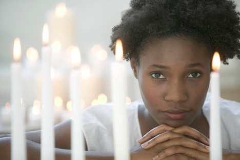 Praying woman surrounded by candles.JPG
